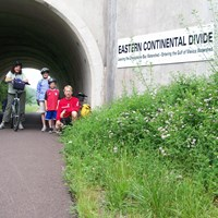 family of bicyclists at the Eastern Continental Divide on the Great Allegheny Passage rail-trail