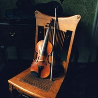 Violin and bow rests against wooden chair.