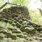 A rock formation that looks like columns stuck together in the woods on a sunny day.