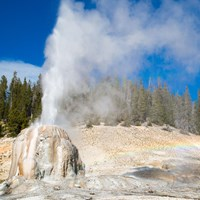 Steam and water erupt from the tan cone of Lone Star Geyser.