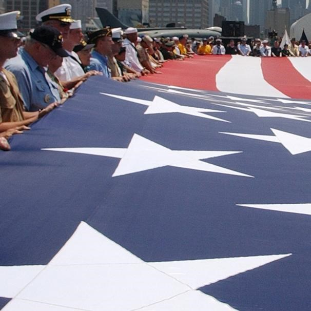 Large American flag held horizontal to the ground by sailors and veterans.