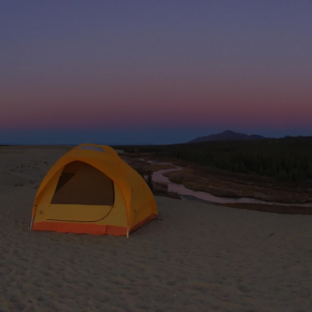Several tents set up on the Great Kobuk Sand Dunes at dusk.