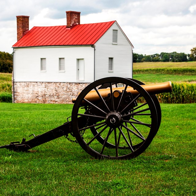 Cannon in field in front of farmhouse.