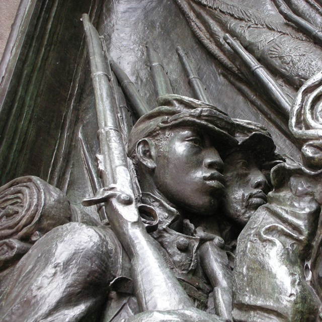 A profile relief of two young soldiers with chiseled features and their equipment.