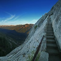 Stone stairs climb a granite peak next to an expansive view of a valley and mountain peaks