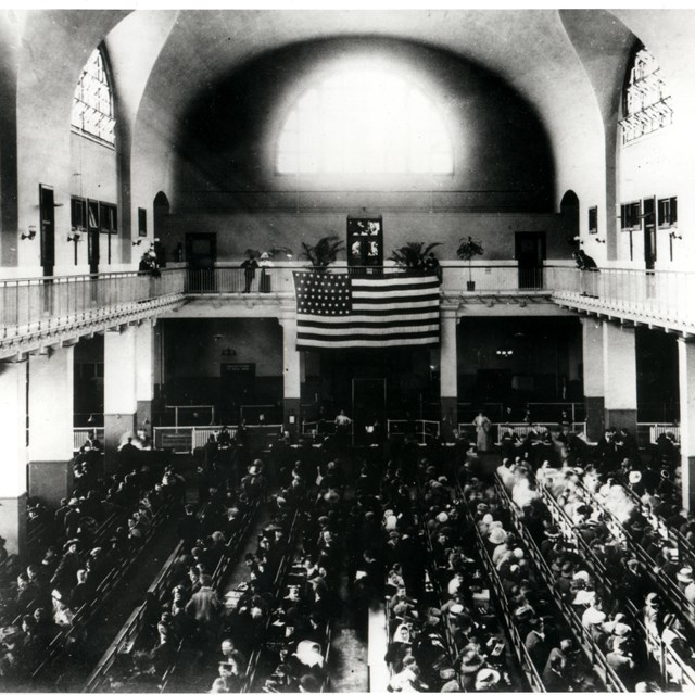 A black and white image of a large hall. An American flag hangs over a throng of people on the floor