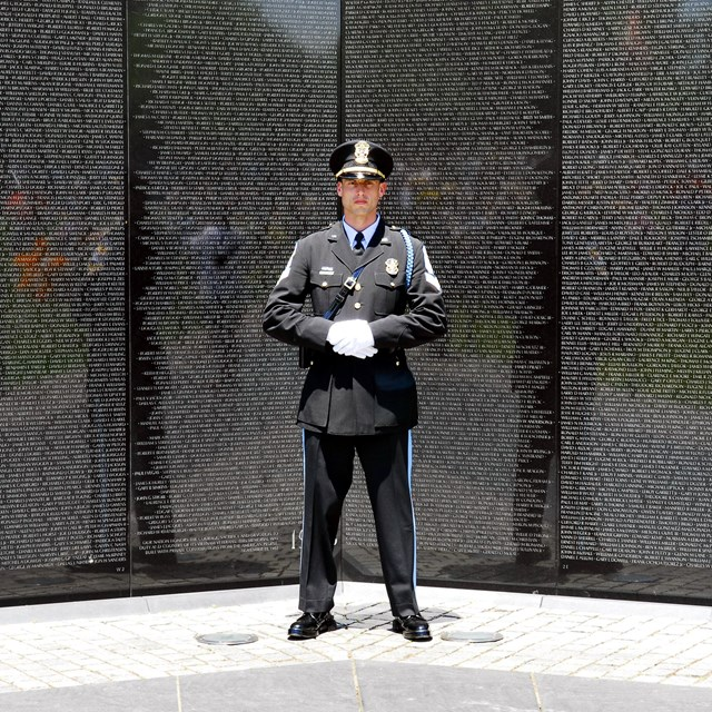 US Park Police Officer standing in front of the Vietnam Veterans Memorial.