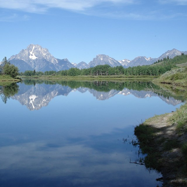 Rocky mountain peaks reflected in a calm lake on a sunny day