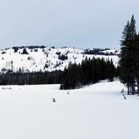 Hills suitable for backcountry skiing circle frozen and snow-covered Cascade Lake.