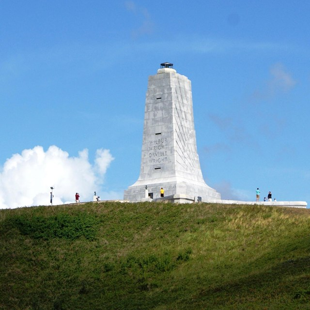 Granite monument atop grassy hill on sunny day