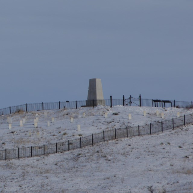 Photograph of hill with monument and headstones with snow on the ground