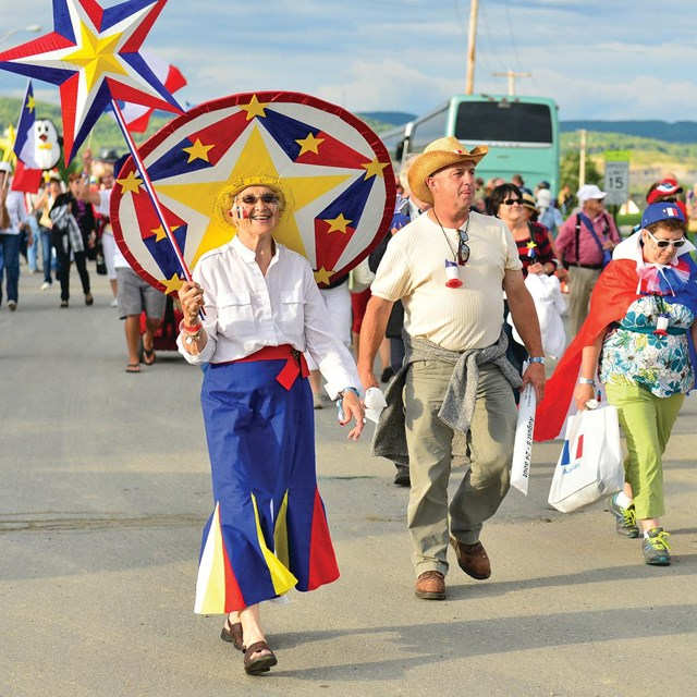 People walking in a parade holding Maine Acadian flags