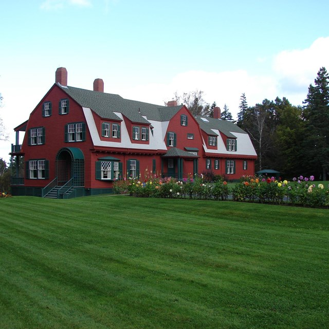 Red cottage on wide grassy lawn