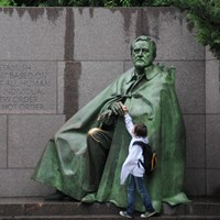 A child reaches up to touch a large bronze statue of Franklin Roosevelt.