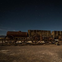 An old wooden wagon train seen at night.