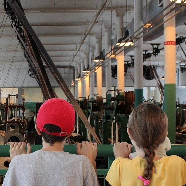 Two young visitors peer over the rail at the looms in the 1910s working weave room at the Boott Mill