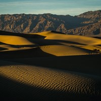 Tawny, shaded dunes extend out to distant desert mountains.