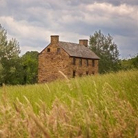 A stone house sits behind a hill in Manassas National Battlefield Park.