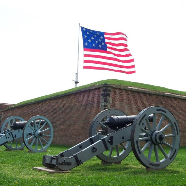 A large American flag waves over the wall of a large brick building. 2 grey cannons face the wall.