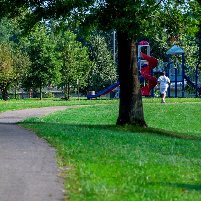 A man runs on a trail going through the park.