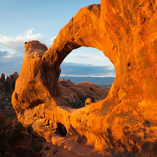 A broad, red rock arch