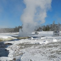 Black Sand Basin thermal features billowing steam along the Firehole River on a cold winter day.