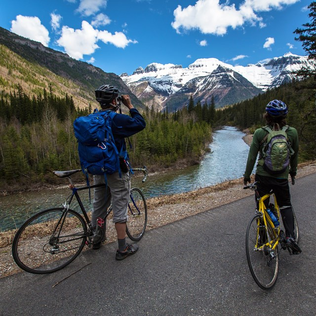 Two bicyclists view mountains from a road along a river
