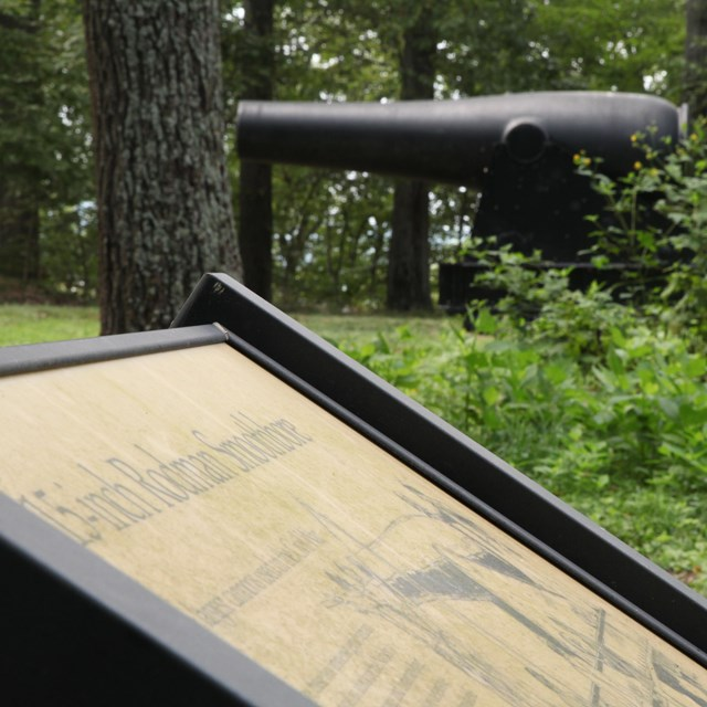 An educational sign and cannon at Fort Foote Park.