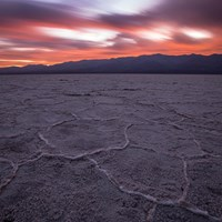 An expansive salt flat with distant desert mountains and a pink sky sunset.