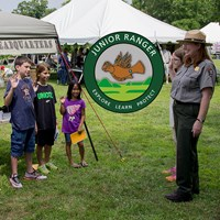 Children stand at attention with hands raised to become park junior rangers