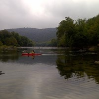 kayaker on a calm, wide river with forested hillsides on both shorelines
