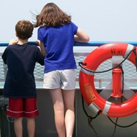 two youth looking at open water from deck of a large boat