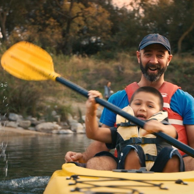 Father and son joyfully paddle a canoe down a wooded calm river