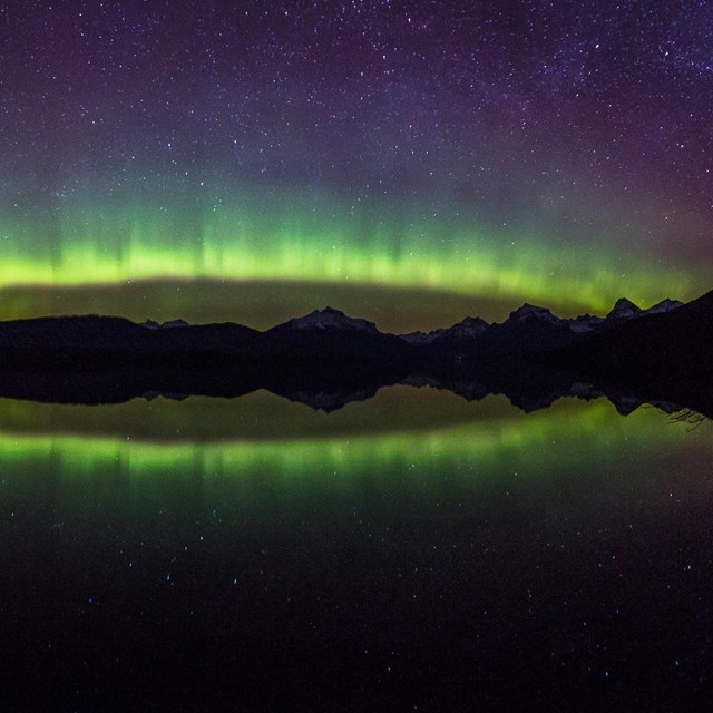The brilliant colors of the aurora borealis arc over a mountain lake