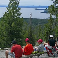 Hikers rest and look out at Yellowstone Lake from atop a mountaintop.