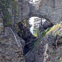 Gray stone rock arches over a creek drainage.