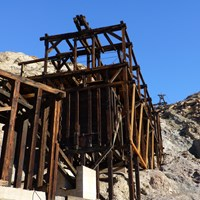A historic wooden tram terminal structure in a desert setting.