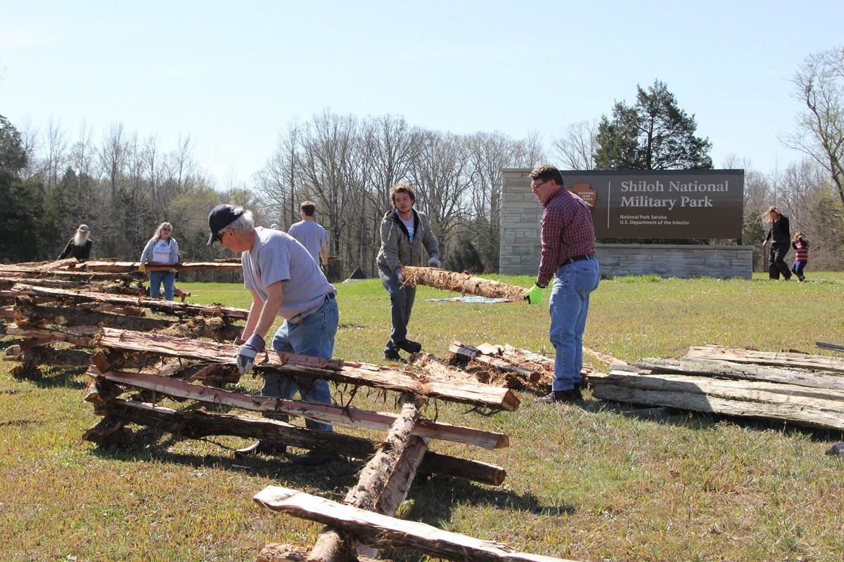 Volunteers building split rail fences