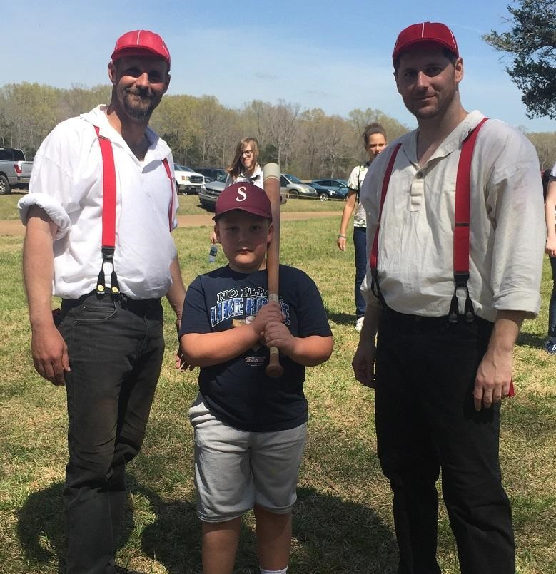 Two vintage base ball players and a young fan.