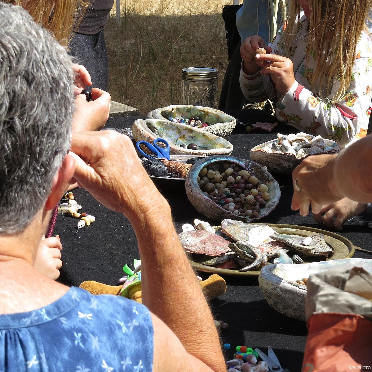 Abalone shells on a table contain various beads. People surrounding the table make bead jewelry.