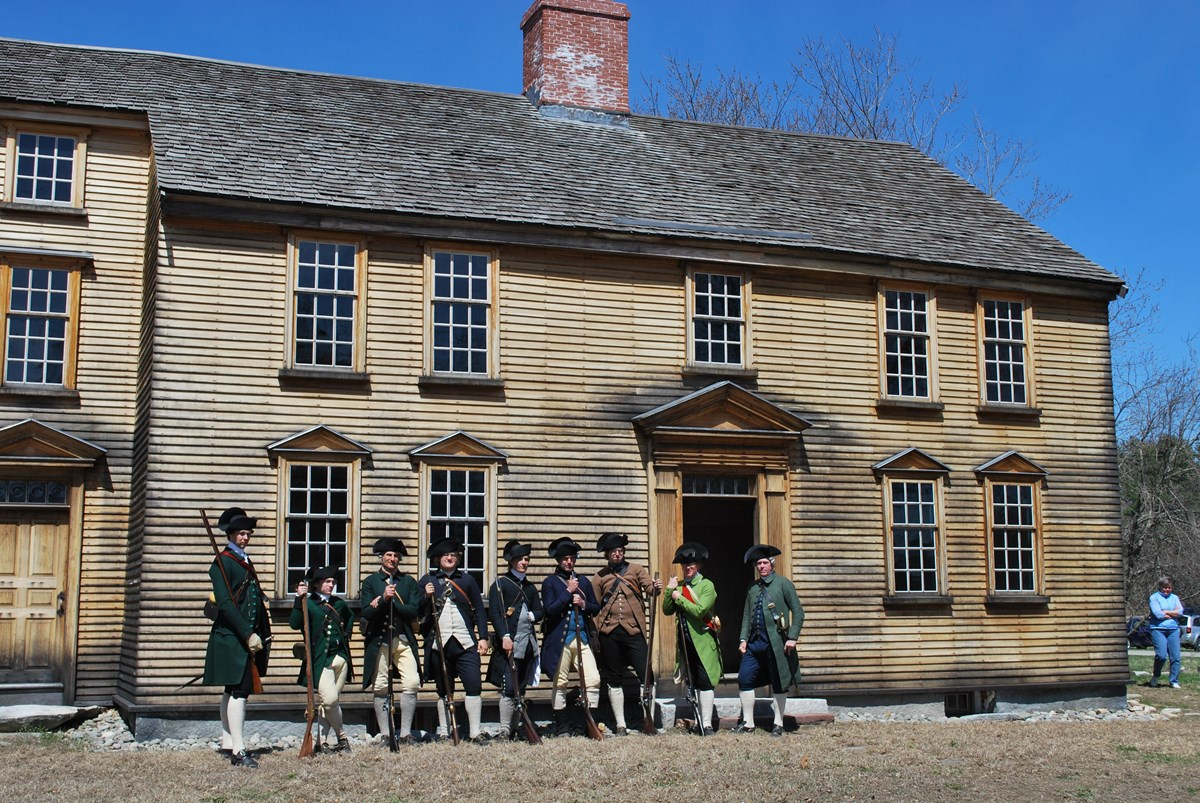 Two story wooden colonial house with people dressed in 18th century clothing in front