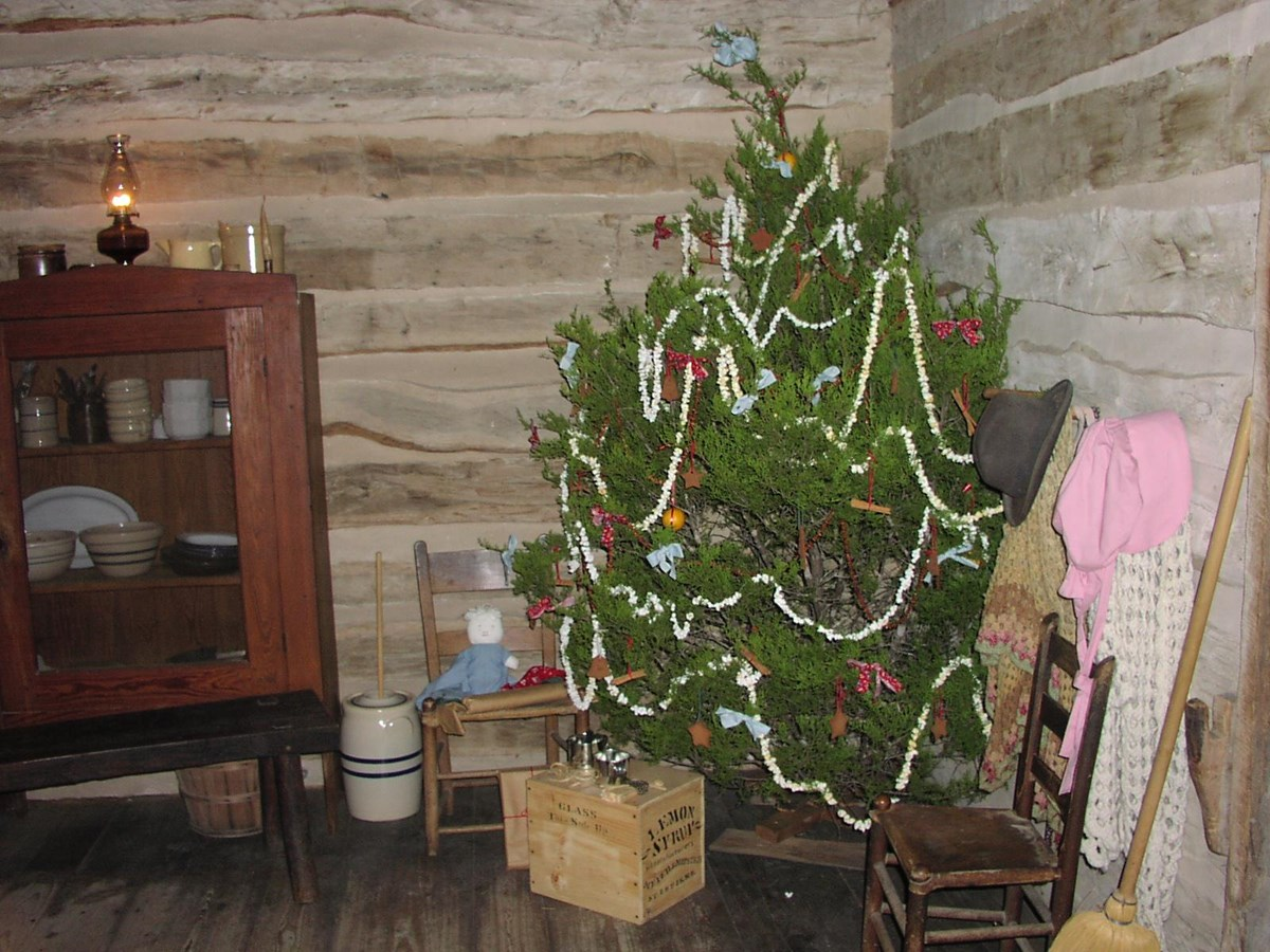 A Christmas tree decorated with popcorn strings stands in the corner of the Johnson log cabin.