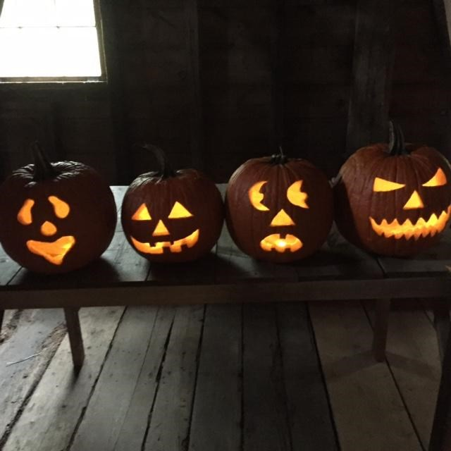 Four lit jack o lanterns on a wooden bench