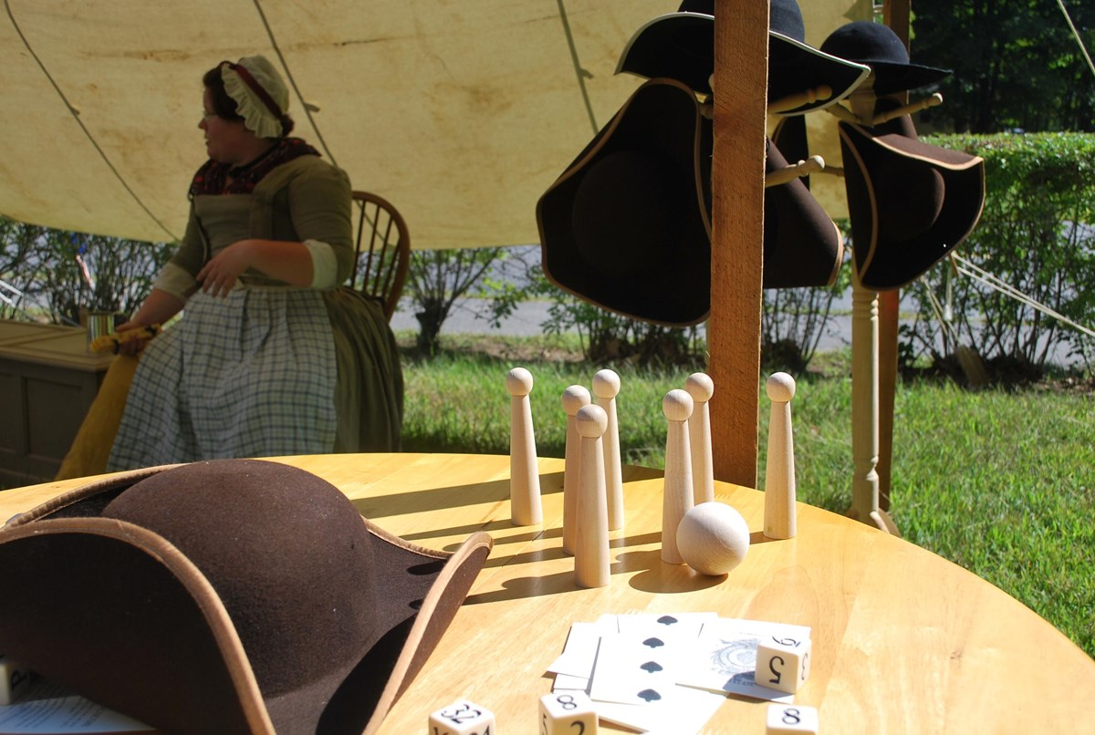 A colonial hat next to a set of tabletop skittles under a canvas awning