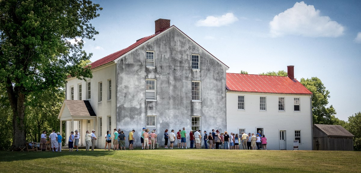Visitors listening to a ranger speak in front of the Thomas House