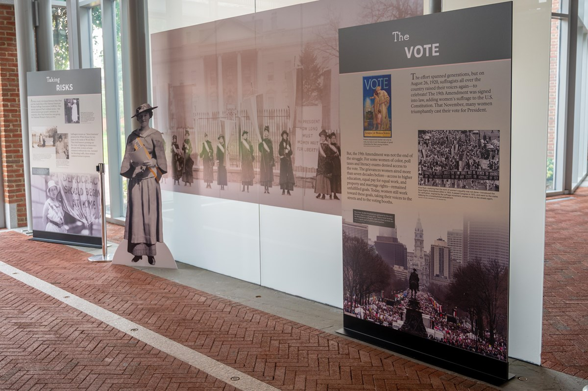 Exhibit panels featuring images and text about women's voting rights flank a cardboard suffragist.