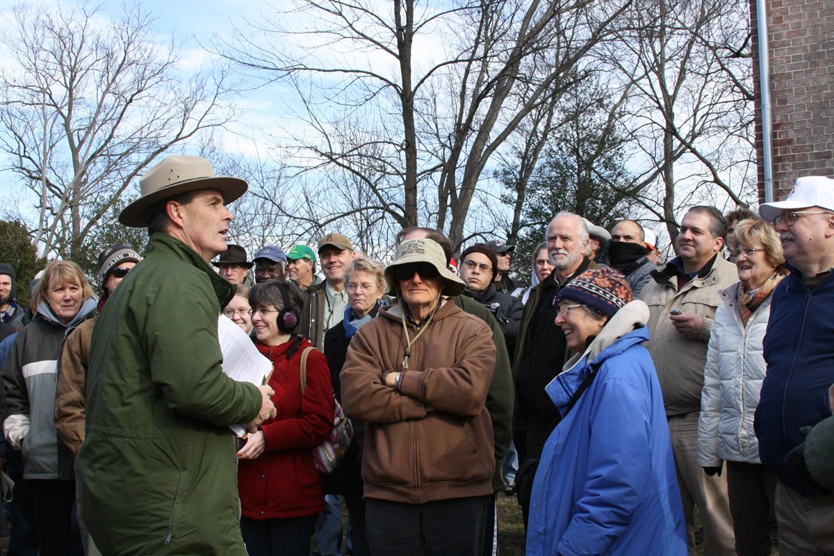 A park ranger speaking outdoors to a large crowd.