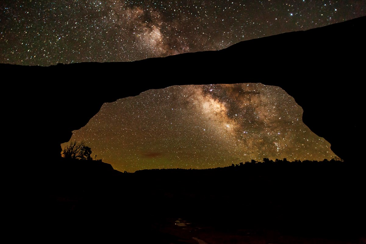 a broad natural stone bridge with the milky way overhead