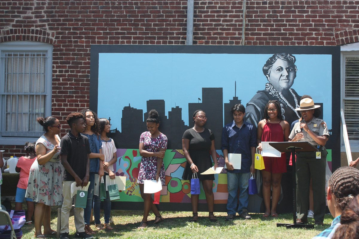 Ranger with students in front of a mural of Maggie L. Walker