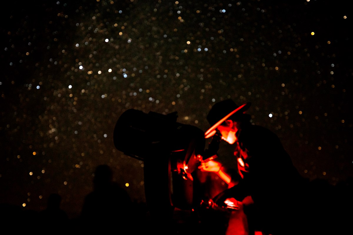 Ranger viewing the night sky through a telescope with numerous stars visible above her